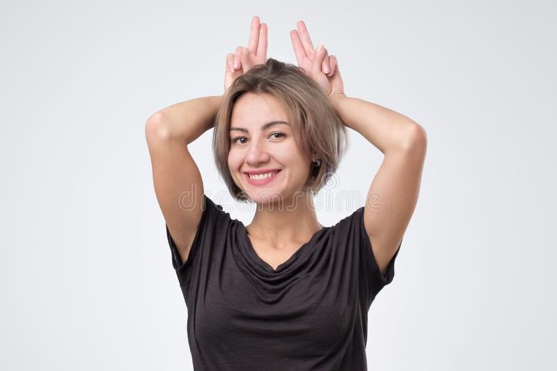 Młoda kobieta robi królików ucho z rękami fotografia stock