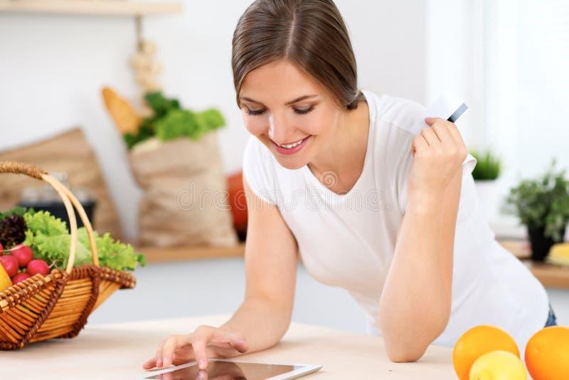 Młoda kobieta robi online zakupy pastylka komputerem i kredytową kartą Gospodyni domowa zakłada nowego przepis dla gotować w a obrazy stock