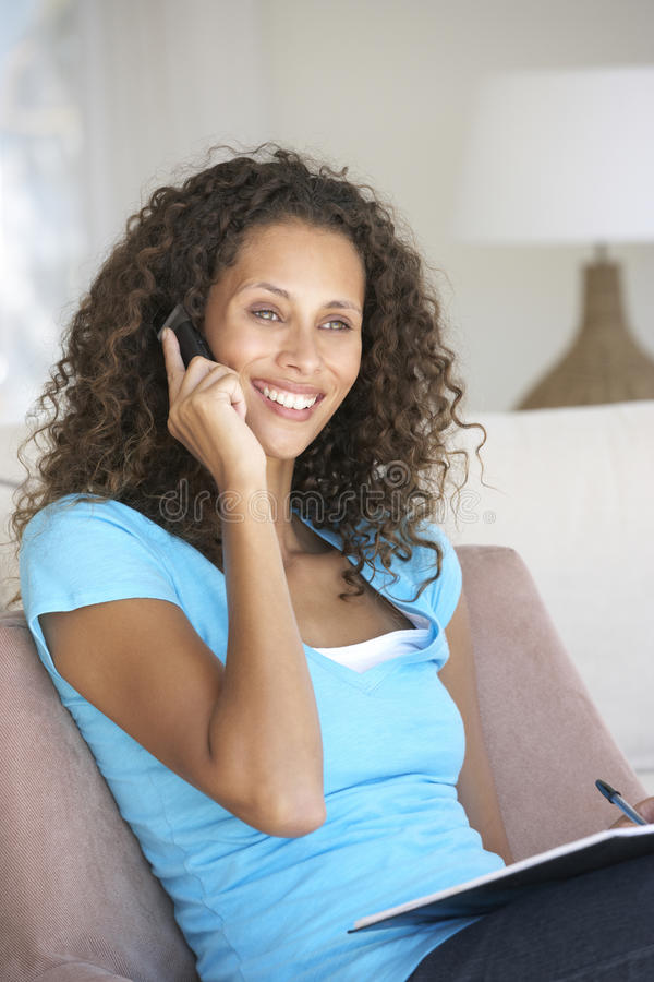 Młoda Kobieta Robi papierkowej robocie I Używa telefon komórkowego W Domu zdjęcia royalty free