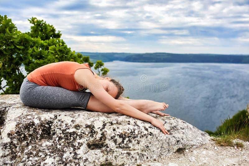 Młoda kobieta robi powikłanemu joga ćwiczeniu na skale nad piękna rzeka fotografia stock