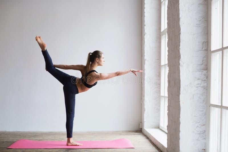Młoda kobieta robi rozciągania ćwiczeniu na joga macie zdjęcia stock