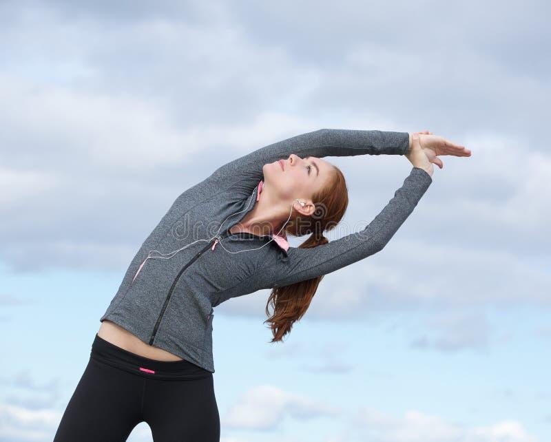 Młoda kobieta robi rozciągliwości ćwiczy outdoors obraz stock