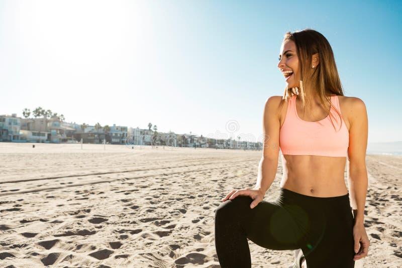 Młoda kobieta robi sportom przy plażą obraz royalty free
