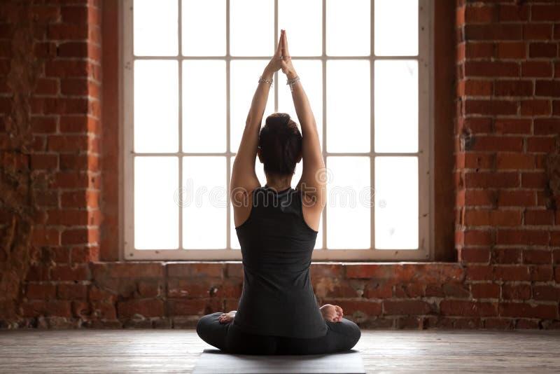 Młoda kobieta robi Sukhasana ćwiczeniu, tylni widok zdjęcie royalty free