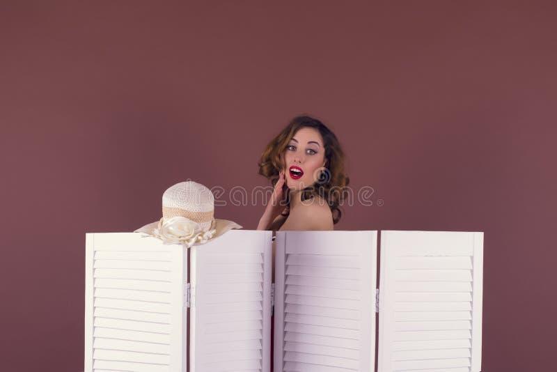 Młoda kobieta rozbiera się za ekranem fotografia stock