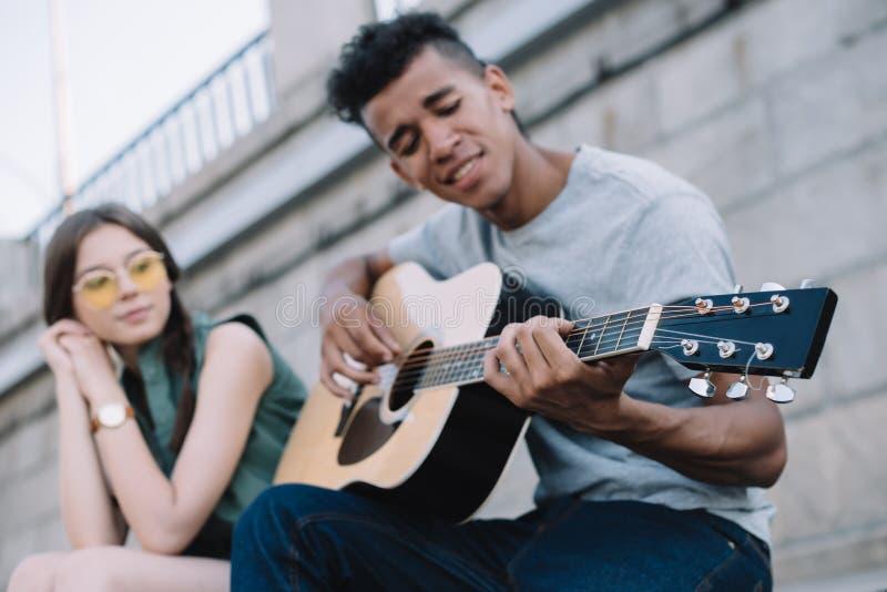 Młoda kobieta słucha amerykanin afrykańskiego pochodzenia facet bawić się gitarę zdjęcie stock