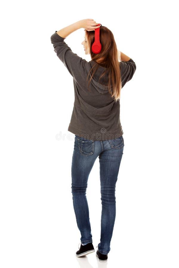 Młoda kobieta słucha muzykę z hełmofonami obrazy stock
