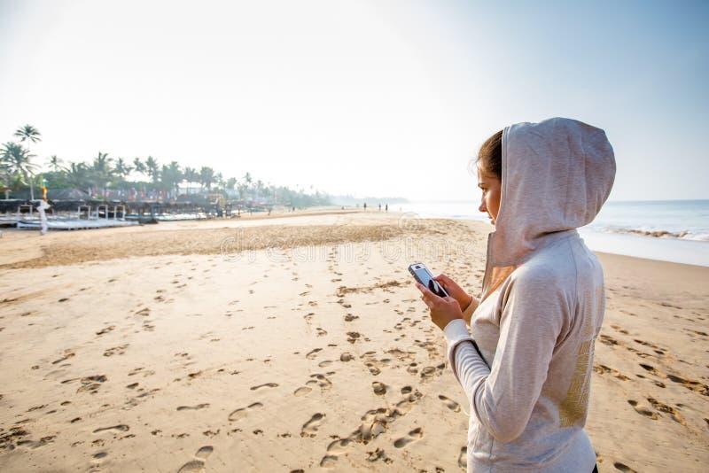 Młoda kobieta słucha muzyka na telefonie przed joggin obraz stock