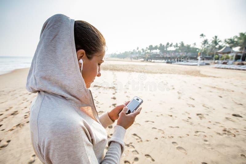 Młoda kobieta słucha muzyka na telefonie przed joggin zdjęcie royalty free