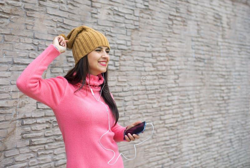 Młoda kobieta słucha muzyka w hełmofonach i tanu blisko bric obraz royalty free