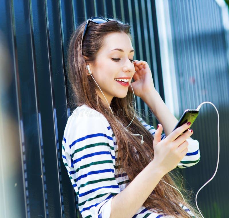 Młoda kobieta słucha muzyka z smartphone zdjęcie stock