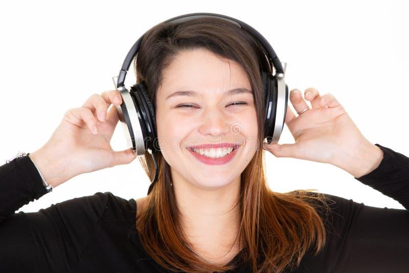 Młoda kobieta słucha muzyki zamykający oczy z hełmofonami cieszy się fotografia stock