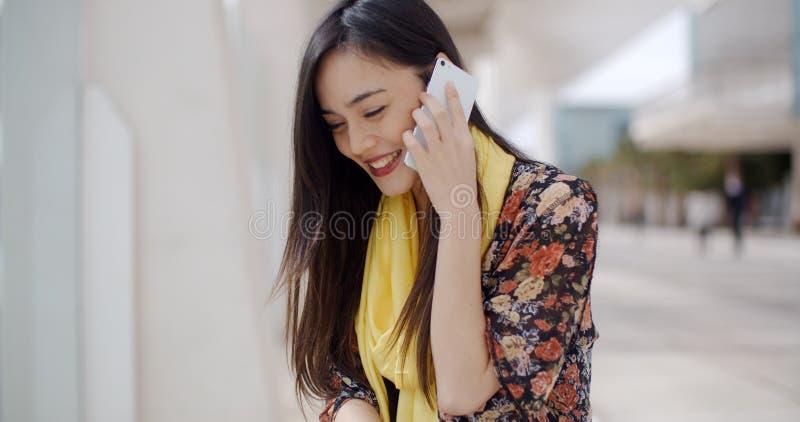 Młoda kobieta słucha a wzywał jej wiszącą ozdobę fotografia stock
