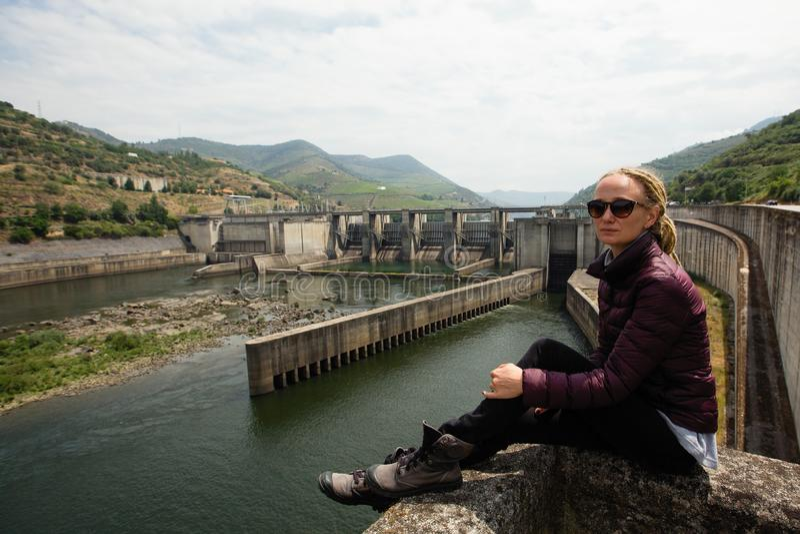 Młoda kobieta siedzi blisko elektrowni w górach z dreadlocks fotografia stock