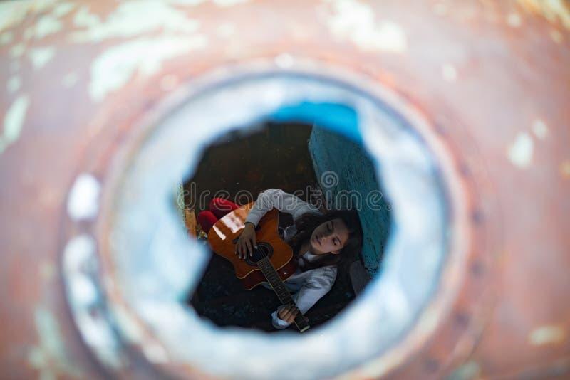 Młoda kobieta siedzi gitarę wśrodku starego zaniechanego statku i bawić się zdjęcia royalty free