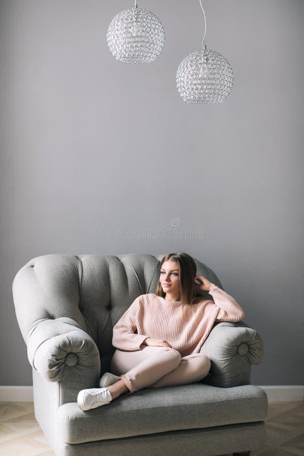 Młoda kobieta siedzi na krzesła relaksować w domu obraz stock