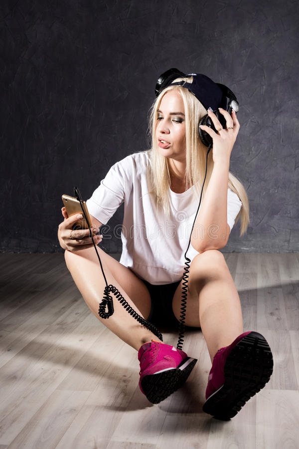 Młoda kobieta siedzi na podłoga blisko ściany z hełmofonami zdjęcie stock