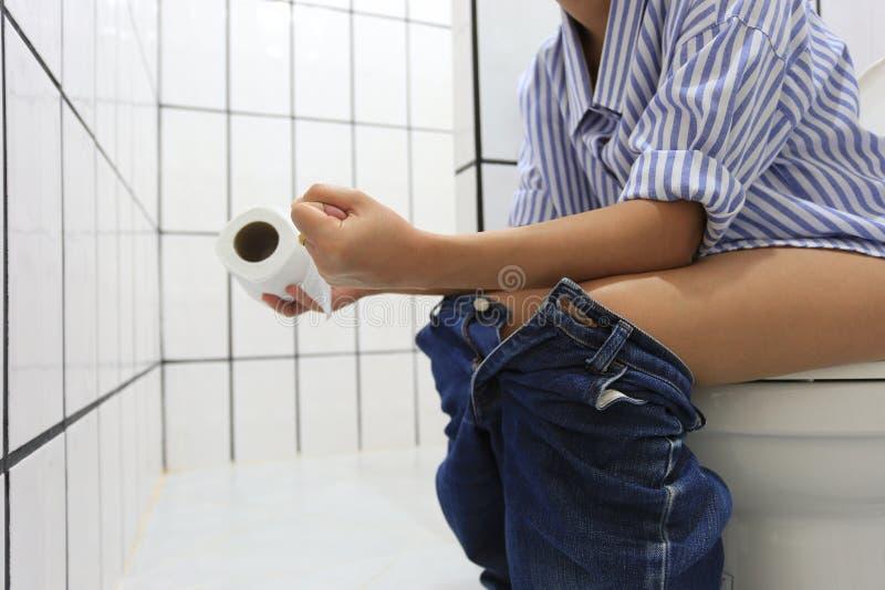 Młoda kobieta siedzi na toalecie zaparcie lub hemoroidy, Zdrowy pojęcie zdjęcia stock