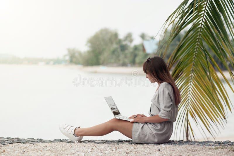 Młoda kobieta siedzi przy działaniem w laptopie i plażą zdjęcia stock