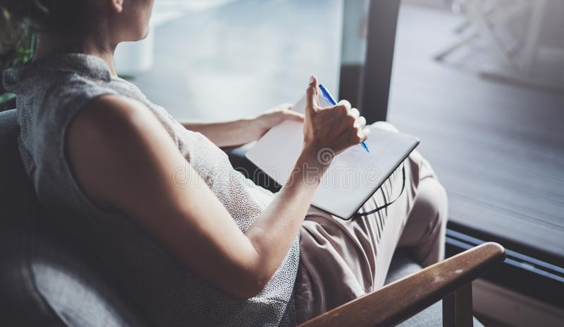 Młoda kobieta siedzi przy stołem w domowym i pisze w notatniku w przypadkowych ubraniach Freelancer działania dom zdjęcie royalty free