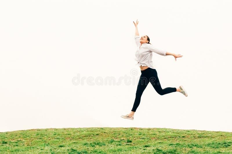 Młoda kobieta, skacze przeciw nieba backgroung, wolności pojęcie obrazy stock