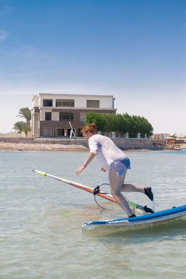 Młoda kobieta spada z deski dla windsurfing w Egipt, Hurgha zdjęcia royalty free