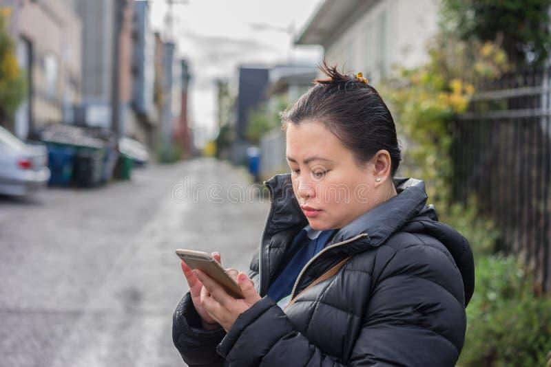 Młoda kobieta sprawdza jej wiadomości jej telefon komórkowy obraz royalty free