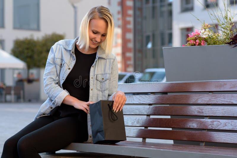 Młoda kobieta sprawdza ona zakupy lub prezent obraz royalty free