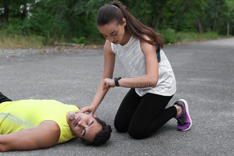 Młoda kobieta sprawdza puls nieświadomie mężczyzna wewnątrz zdjęcia stock