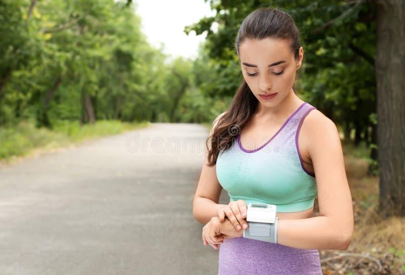 Młoda kobieta sprawdza puls z medycznym po trenować w parku Przestrze? dla obrazy stock