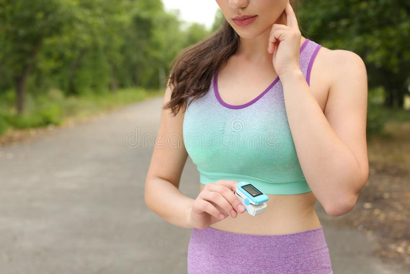 Młoda kobieta sprawdza puls z przyrządem po tym jak trenujący w parku, zbliżenie Przestrze? dla teksta obrazy royalty free