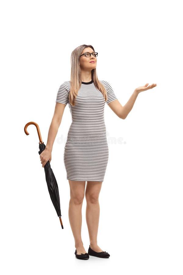 Młoda kobieta sprawdza widzieć z parasolem jeżeli ja pada obraz stock