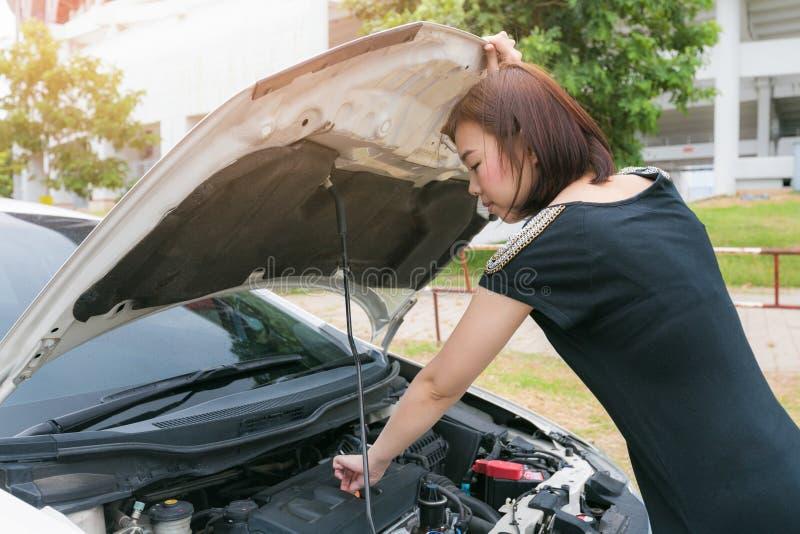 Młoda kobieta sprawdza z naprawiać jej łamanego samochód obraz royalty free