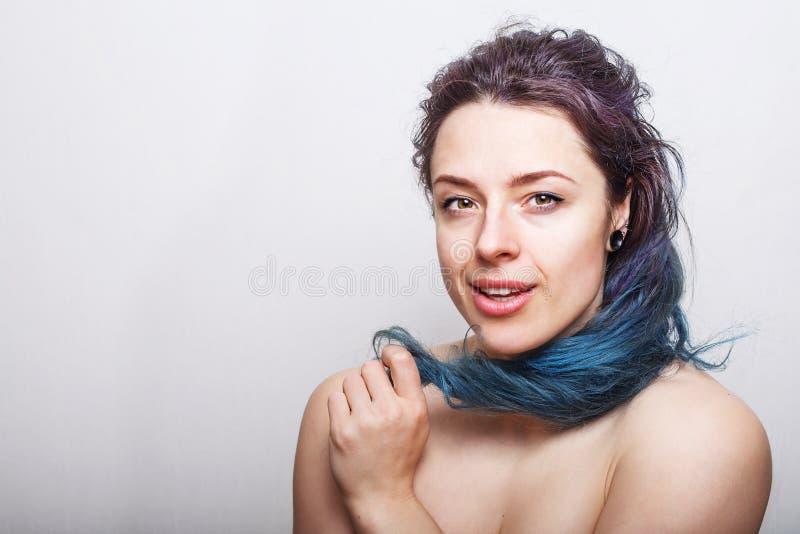 Młoda kobieta stacza się jej kolorowego ale uszkadzającego upaćkanego włosy na jej palcu zdjęcie stock