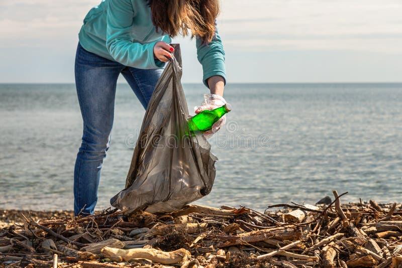 Młoda kobieta stawia zbierającego śmieci w torbie Czyścić ochrona środowiska i terytorium obraz stock