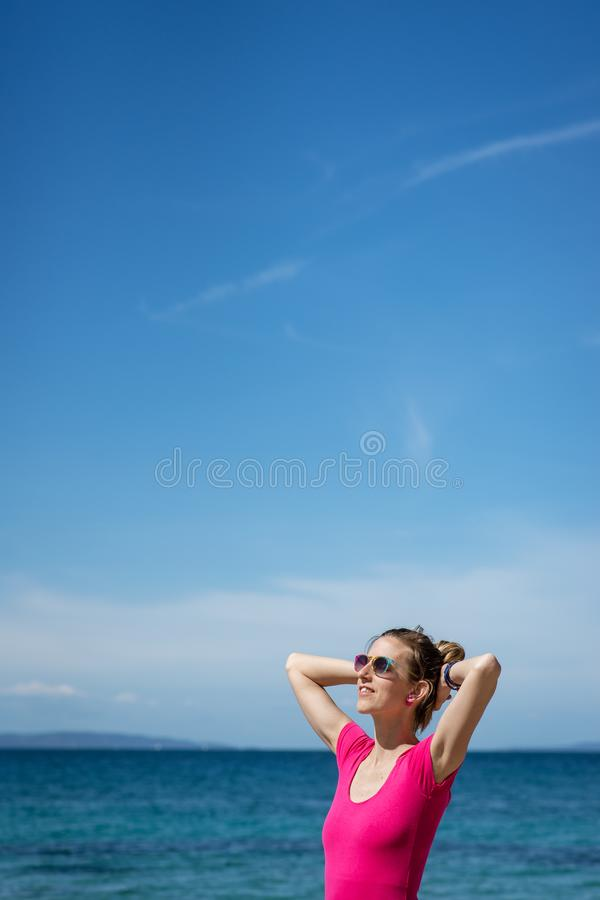 M?oda kobieta stoi bezczynnie morze w r??owej koszula zdjęcie stock