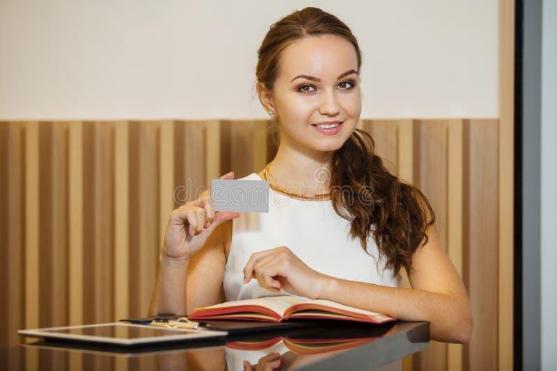 Młoda kobieta stoi blisko stołu i trzyma wizytówkę fotografia royalty free