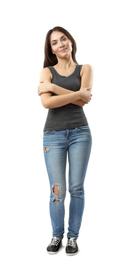 Młoda kobieta stoi z rękami w szarym sleeveless wierzchołku i niebieskich dżinsach krzyżował przy klatką piersiową odizolowywając zdjęcie royalty free
