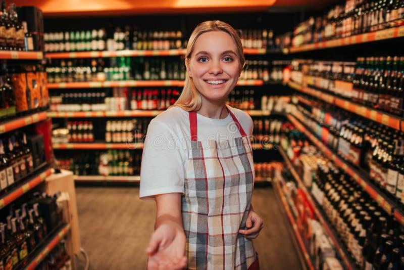 Młoda kobieta stojak w alkoholów shelfs w sklepie spożywczym Ona reaxh ręka kamera i uśmiech Rozochocona szczęśliwa młoda kobieta obrazy stock