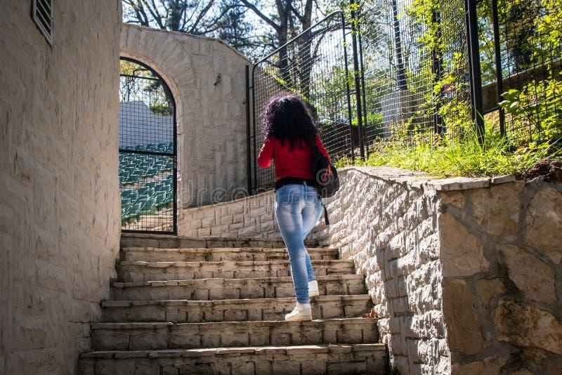Młoda kobieta stojaki na kamiennych schodkach zdjęcia royalty free