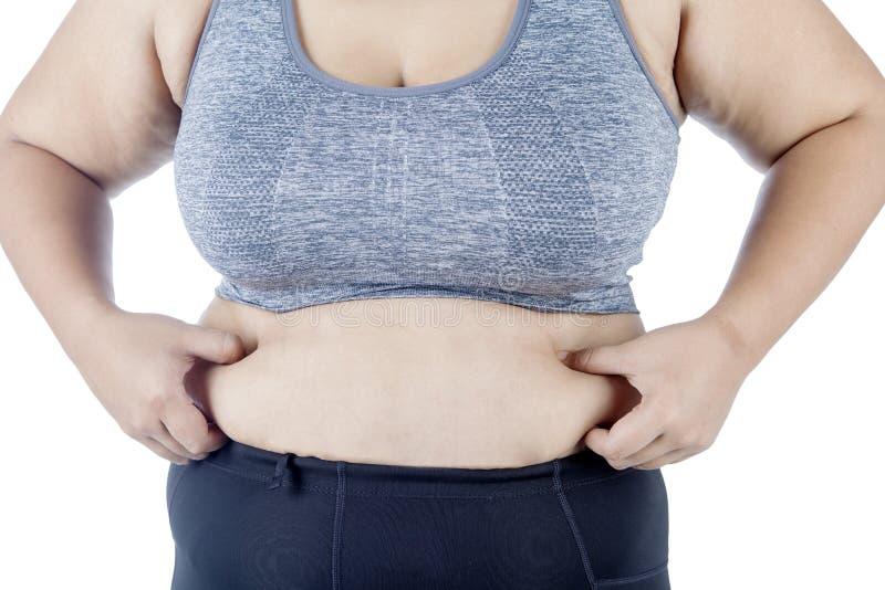 Młoda kobieta szczypa jej brzucha na studiu zdjęcie royalty free
