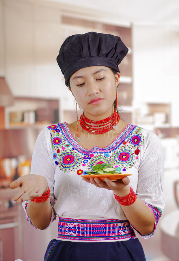 Młoda kobieta szef kuchni jest ubranym tradycyjną andyjską bluzkę, czarny kulinarny kapelusz, mienia ogórkowi plasterki talerz, s zdjęcia stock
