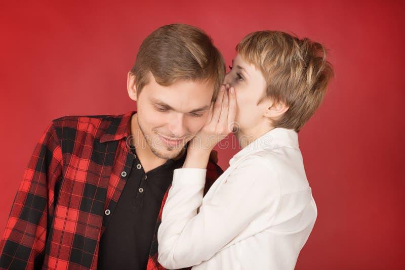 Młoda kobieta szepcze sekret uśmiechnięty mężczyzny ucho obraz stock