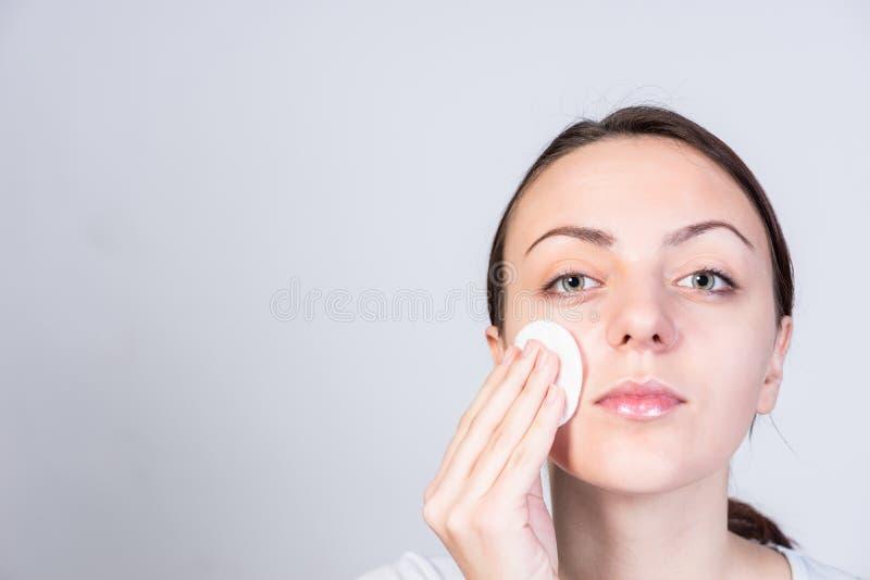 Młoda Kobieta Szoruje jej twarz z Astringent zdjęcie stock