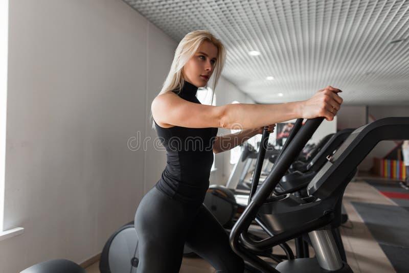 Młoda kobieta trener z pięknym ciałem w czerni ubraniach trenuje na symulancie w sprawność fizyczna pokoju Dziewczyna w gym obrazy stock