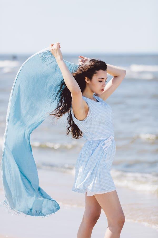 Młoda kobieta trzyma błękitnego falowanie szalika obraz stock