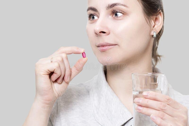 Młoda kobieta trzyma czerwoną witaminy pastylkę i szkło woda Co fotografia stock