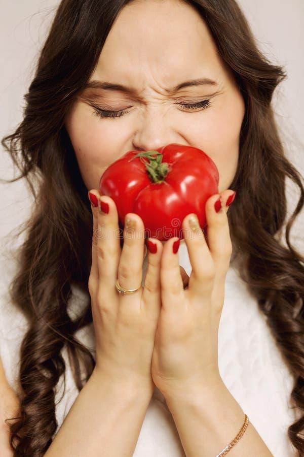 Młoda kobieta trzyma dojrzałego soczystego pomidoru w ręce, w górę fotografia stock