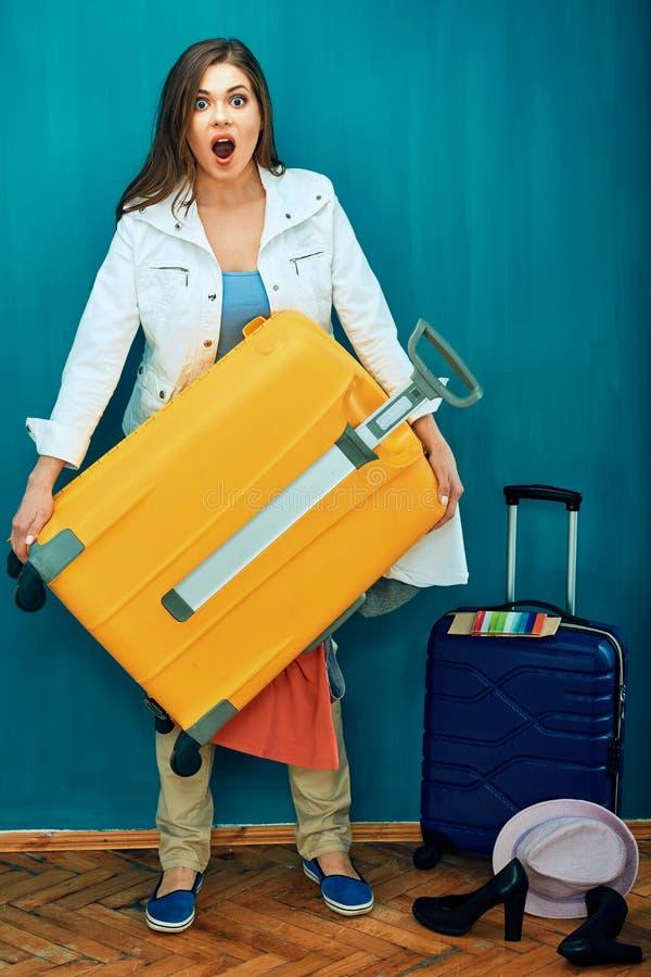 Młoda kobieta trzyma dużą wagi ciężkiej walizkę
