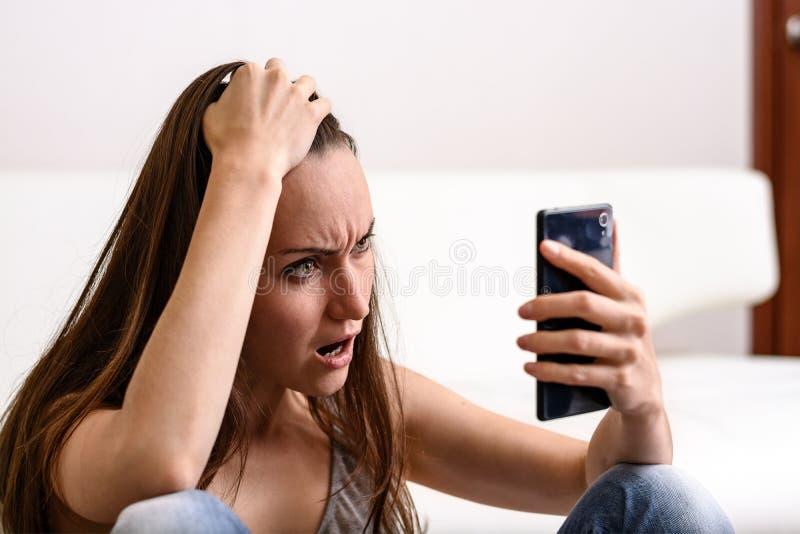 Młoda kobieta trzyma jego spojrzenia i głowę smartphone Martwiący co zobaczył fotografia royalty free